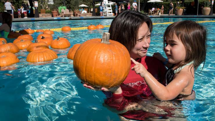 woman with young girl in water pumpkin diving