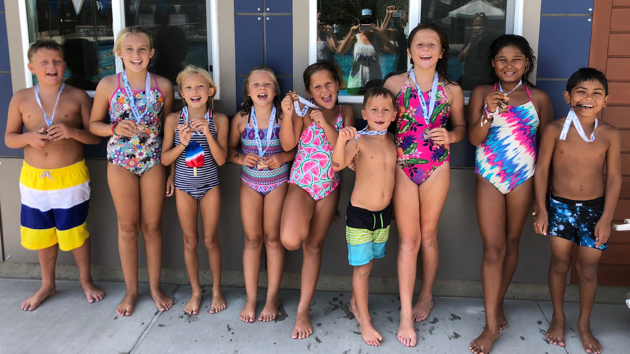 group of young children in bathing suits posing for photo