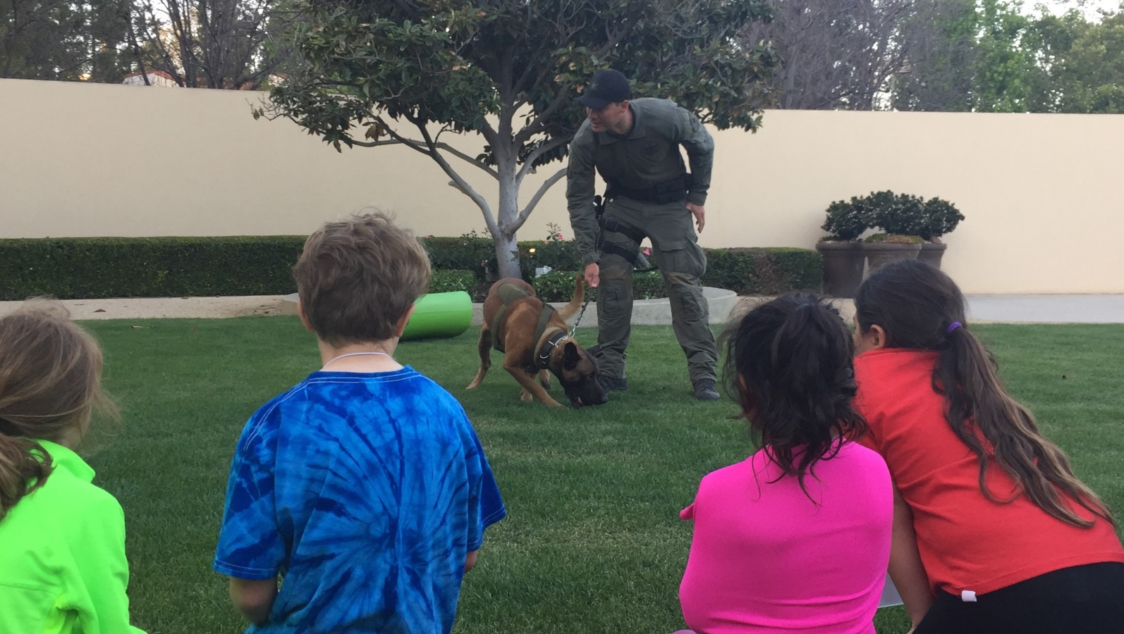 officer with training dog and young children