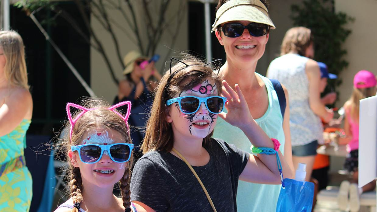 2 girls wearing face paint, cat ears and sunglasses with mom