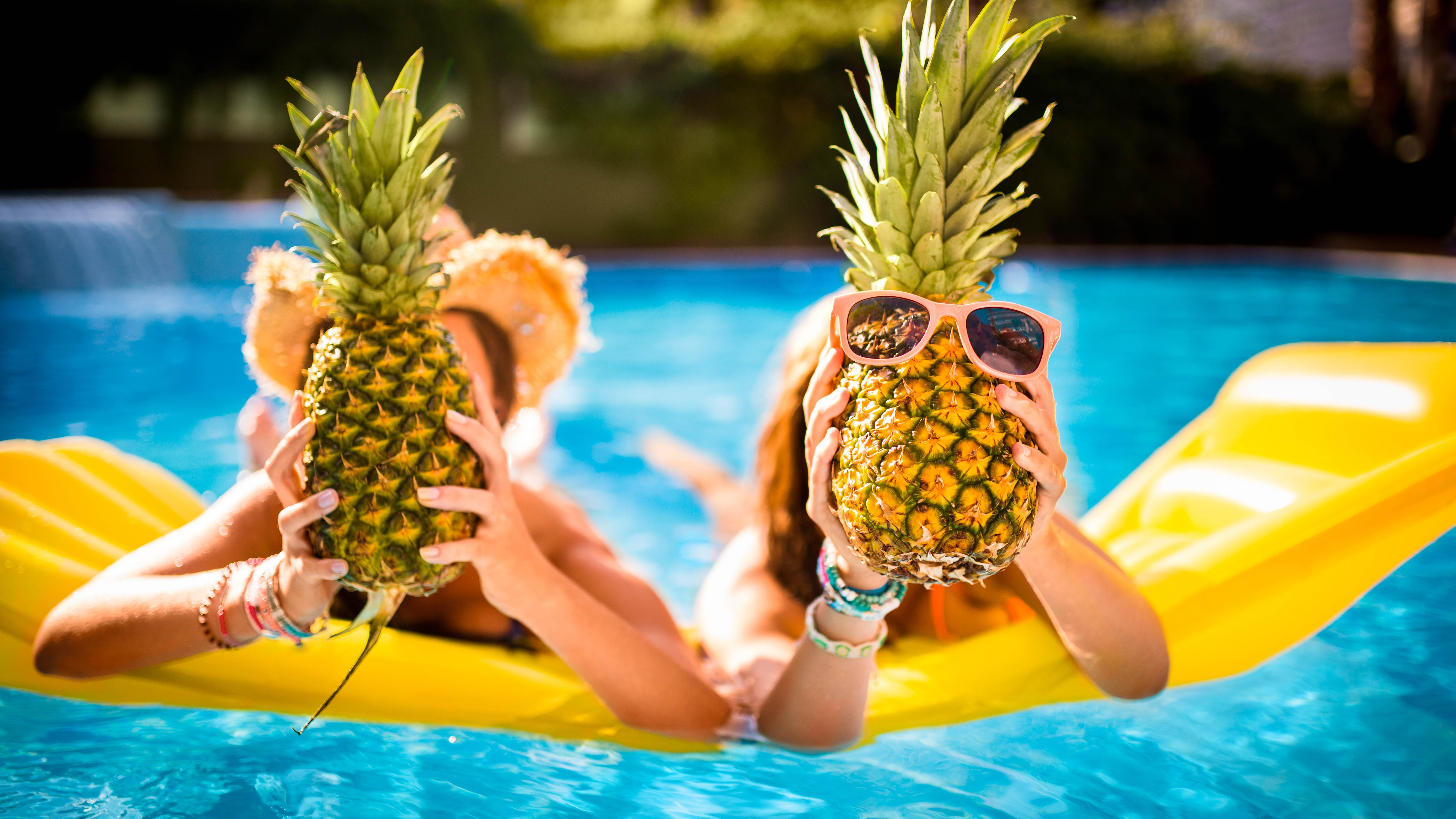people on floatie in pool holding pineapples
