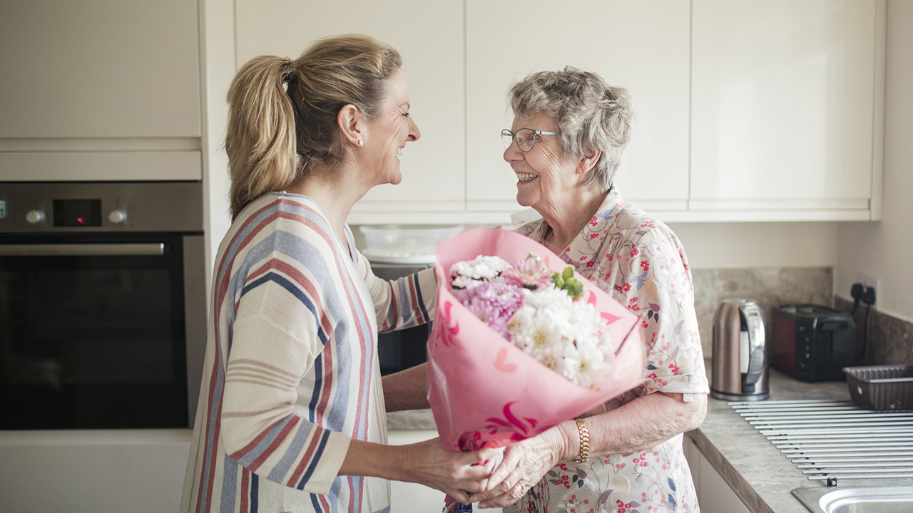 adult woman giving flowers to senior woman