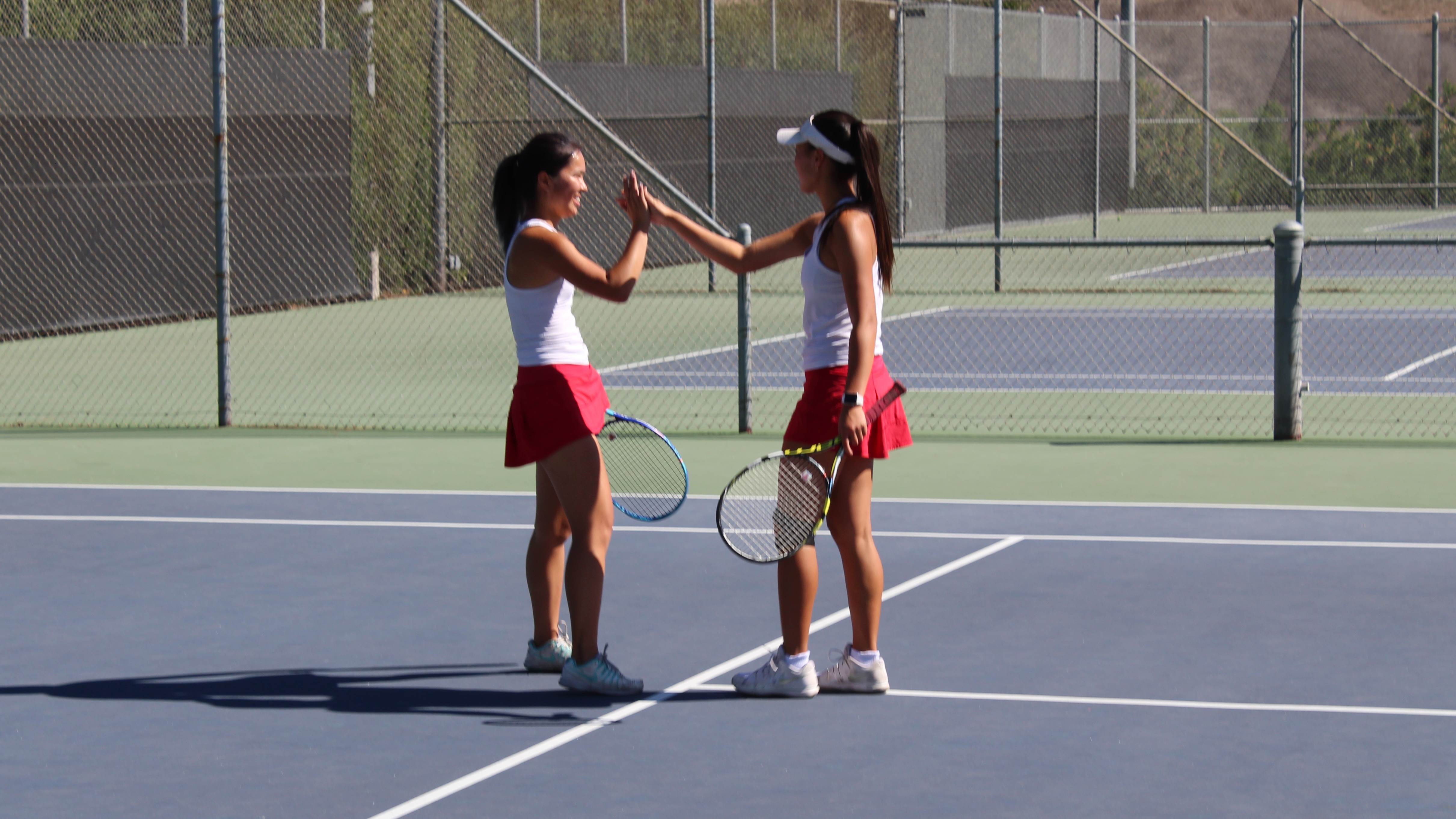 girls high-fiving on tennis court