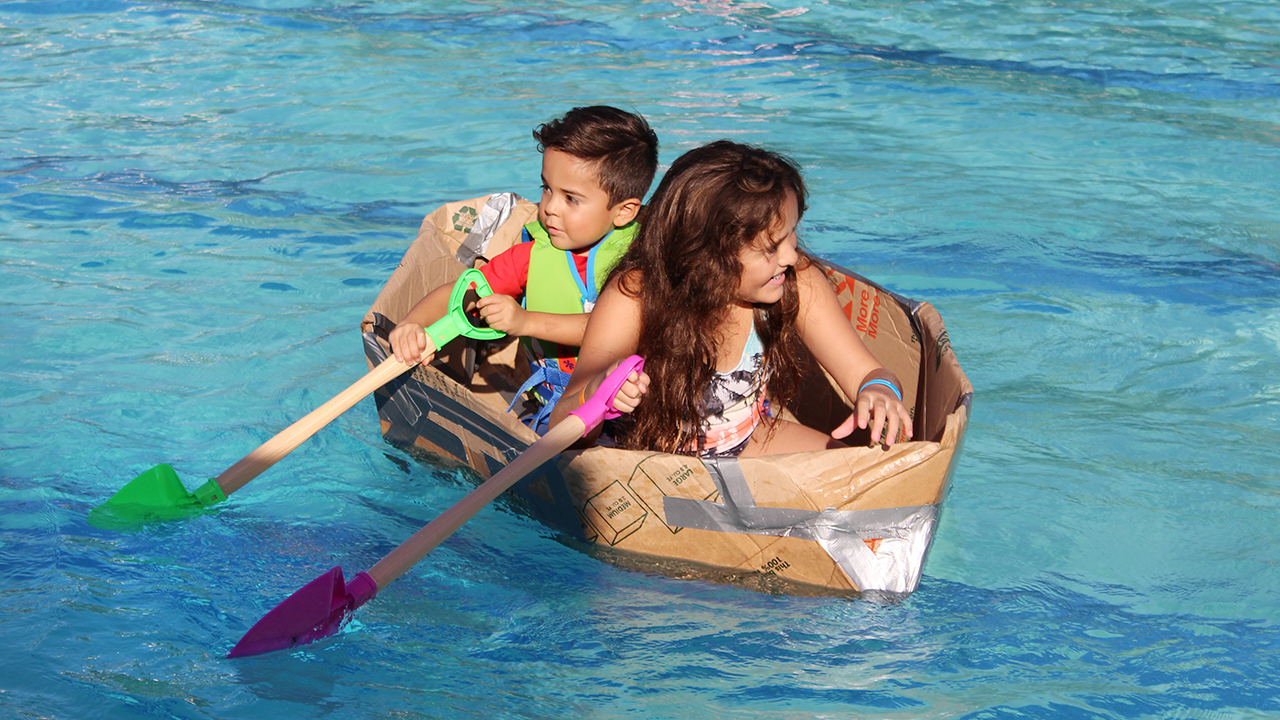 2 kids in cardboard boat in pool