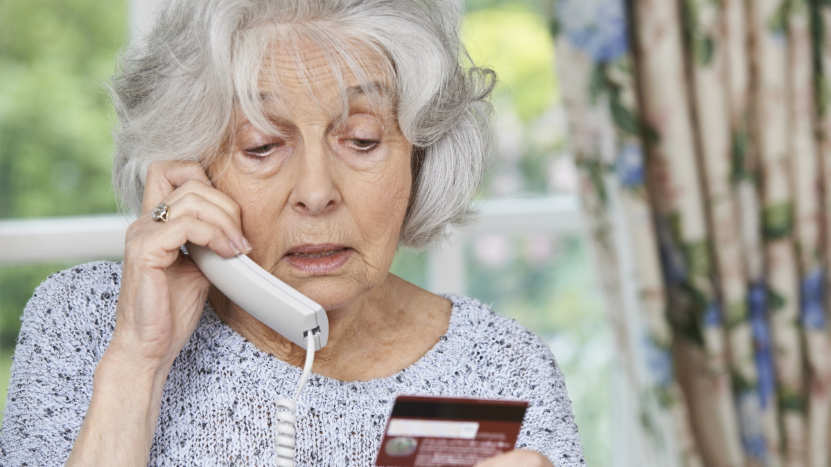 senior with credit card on phone