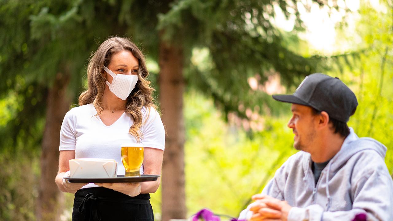 waitress wearing mask serving outside