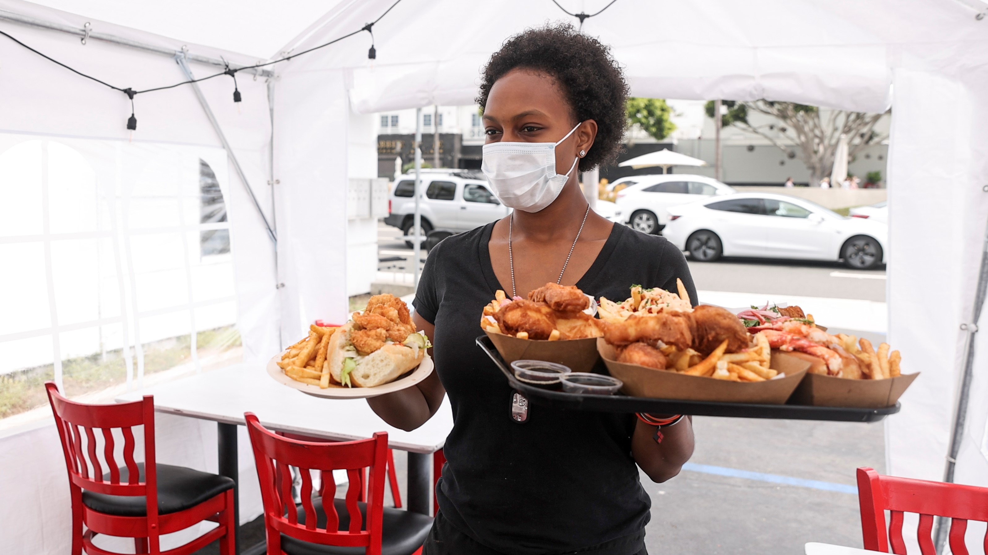 woman in mask serving food outside